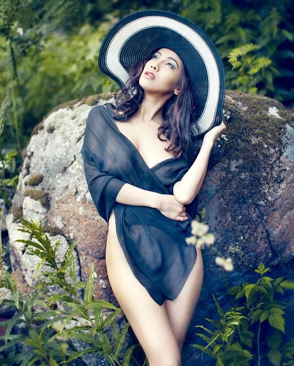 женщина в шляпке стоит у камня