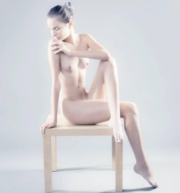 Девушка с красивым телом сидит на стуле.
