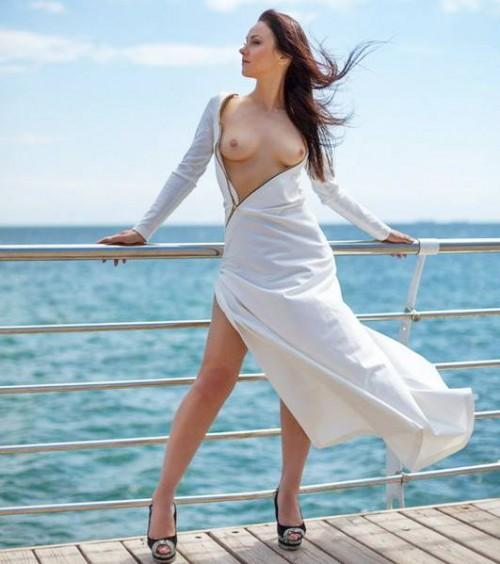 Девушка стоит на пристани на фоне голубого моря